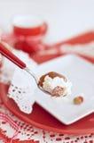 Babza con una crema e le fragole sui colori rossi e bianchi del cucchiaio Immagini Stock
