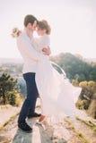 新郎和柔和的新娘佩带的白色礼服有吸引力的年轻爱恋的夫妇振翼在风的站立在晴朗的室外bac 免版税库存图片