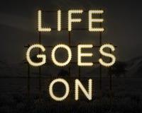 Жизнь идет дальше воодушевить текст в светах против темного bac ландшафта Стоковые Фото