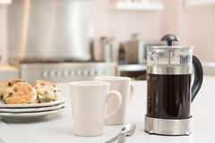 Bac de café sur le compteur de cuisine avec des scones image libre de droits