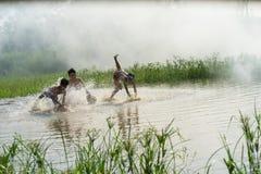 Bac Ninh, Vietnam - 29 maggio 2016: Bambini che pescano pesce pescando trappola di bambù - il vecchio modo tradizionale, sullo st immagine stock libera da diritti