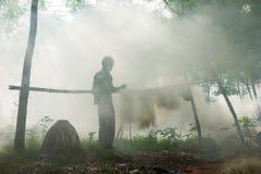 Bac Ninh, Vietnam - 29 maggio 2016: Rete del pesce di riparazione del pescatore dal fiume di Cau sotto fumo pesante dal fuoco del fotografie stock libere da diritti