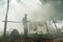Bac Ninh, Vietnam - May 29, 2016: Fisherman mending fish net by Cau river under heavy smoke from discard rice straw fire.  Royalty Free Stock Photos