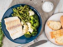 Bacalao cocido de los pescados de mar con las verduras en la placa azul, pan, fotos de archivo