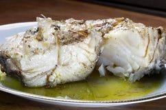 Bacalao cocido en un plato blanco Fotos de archivo libres de regalías
