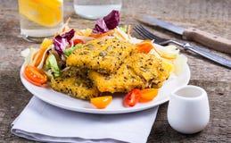 Bacalao frito con la ensalada foto de archivo