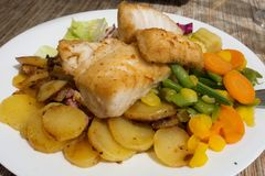 Bacalao frito con las patatas asadas y las verduras guisadas Foto de archivo