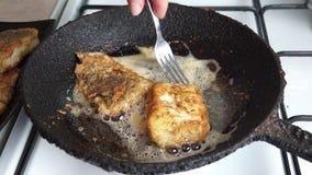 Bacalao frito estropeado en una sartén del arrabio rústica metrajes