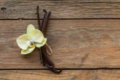 Baccelli della vaniglia e fiori secchi della vaniglia dell'orchidea su fondo di legno Zucchero vanigliato immagini stock