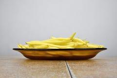Baccelli di fagiolo giallo sulla lastra di vetro, fondo bianco Fotografia Stock Libera da Diritti