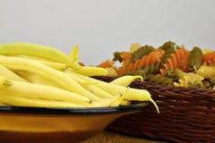 Baccelli di fagiolo giallo sulla lastra di vetro, pasta a tre colori in una ciotola di vimini Fotografie Stock Libere da Diritti