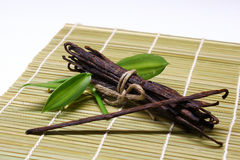 Baccelli di vaniglia con la foglia su bambù Immagine Stock