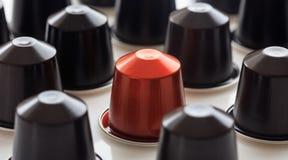 Baccello rosso del caffè del caffè espresso fra i baccelli neri su fondo bianco, vista del primo piano con i dettagli Immagini Stock Libere da Diritti