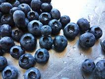 Bacche blu bagnate rovesciate sul contatore Fotografie Stock