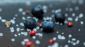 Bacche del mirtillo con il primo piano dei granelli dello zucchero su un fondo scuro immagini stock