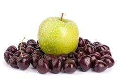 Bacche della ciliegia ed una grande mela verde sulla fine isolata fondo bianco sulla macro fotografia stock