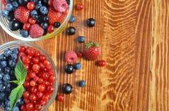 Bacche di rosa-rosso blu nero su fondo di legno marrone immagine stock