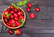 Bacche fresche delle fragole e delle ciliege su un fondo di legno Immagini Stock Libere da Diritti