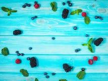 Bacche fresche di estate, strutture d'angolo su fondo di legno blu Immagine Stock