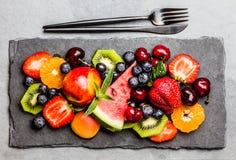 Bacche fresche e frutti di estate dell'assortimento sul piatto nero dell'ardesia fotografia stock