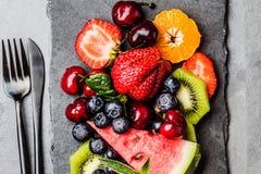 Bacche fresche e frutti di estate dell'assortimento sul piatto nero dell'ardesia fotografia stock libera da diritti