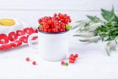 Bacche mature del ribes in tazza bianca e fiori su un fondo bianco Fotografia Stock