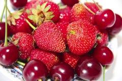 bacche rosse delle fragole e delle ciliege di Borgogna con le foglie su un piatto isolato su fondo bianco fotografia stock