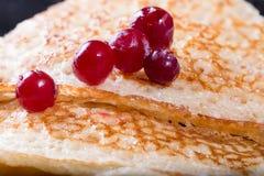 Bacche rosse di un mirtillo rosso su un pancake dorato fritto Fotografia Stock