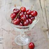 Bacche rosse fresche delle ciliege in vaso a cristallo d'annata sulla vecchia tavola di legno rustica Fotografia Stock Libera da Diritti
