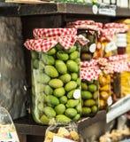 Bacche verde oliva d'inscatolamento casalinghe Intere olive verdi nella latta di vetro sugli scaffali immagini stock