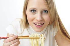 Bacchette bionde di uso della donna che mangiano le tagliatelle Immagini Stock