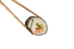 Bacchette che tengono un rullo di sushi Fotografia Stock Libera da Diritti