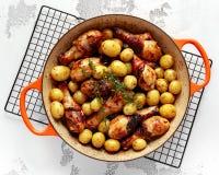 Bacchette di pollo al forno del forno e nuove patate del bambino con timo in pentola, pronta da servire fotografia stock libera da diritti