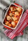 Bacchette di pollo al forno in salsa con i pomodori, la cipolla e il garli Fotografia Stock Libera da Diritti