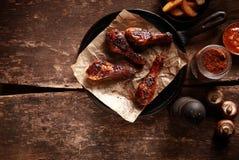Bacchette di pollo arrostite col barbecue impertinenti sulla pentola del ferro Immagine Stock