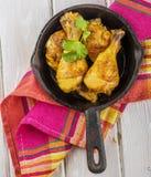 Bacchette di pollo arrostite in pentola su un di legno Fotografia Stock
