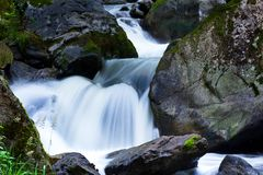 Bach in the water with stones and mountains. A cool stream of water and rocks in the mountains. Unspoiled nature royalty free stock photography
