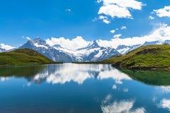 Bachalpsee ed i picchi della neve della regione di Jungfrau Fotografia Stock