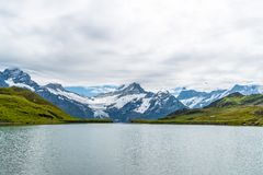 Bachalpsee lake with Schreckhorn and Wetterhorn at Grindelwald in Switzerland. Bachalpsee lake with cloudy ,Schreckhorn and Wetterhorn at Grindelwald in royalty free stock photography