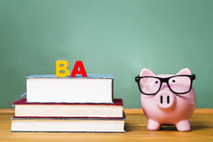 Bachelor of Arts degree theme with textbooks and piggy bank Stock Photos