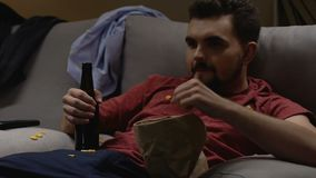 Bachelor drinking beer with snacks and watching sports channels, weekend leisure stock video footage