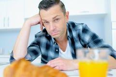 Bachelor eating breakfast alone Stock Images