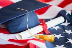 Bachelor hat and diploma on american flag Stock Image