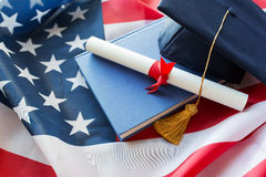 Bachelor hat and diploma on american flag Stock Images