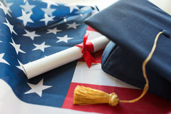 Bachelor hat and diploma on american flag Royalty Free Stock Images