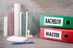 Bachelor and Master. Binders on desk in the office. Business background Stock Photos