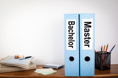 Bachelor and Master binders in the office. Stationery on a wooden shelf Royalty Free Stock Photos
