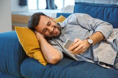 Bachelor man daily routine in the living room single lifestyle concept holding smartphone smiling stock images