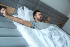 Bachelor man daily routine single lifestyle morning concept awakening stretching Royalty Free Stock Photography