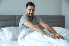 Bachelor man daily routine single lifestyle morning concept awakening stretching sleepy Stock Photo